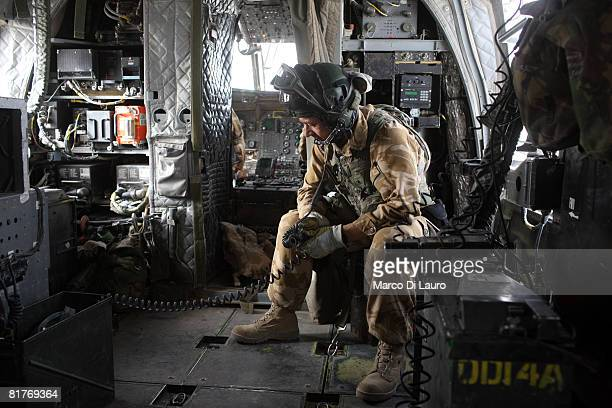 Chinook 27th Squadron Royal Air Force air crew member part of the Joint Helicopter Force sits on board a Chinook helicopter as troops and supplies...