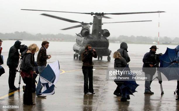 A Chinook helicopter blows the media's umbrellas inside out as it lands at the launch of Royal International Air Tattoo at RAF Fairford Gloustershire