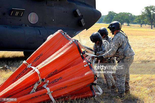 CH-47 Chinook helicopter crew prepare to install the Bambi Bucket on the aircraft.