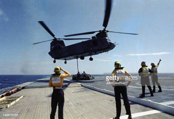 A Chinook helicopter lifts supplies from a helipad on board the Cunard liner 'RMS Queen Elizabeth 2' which has been requisitioned as a British...