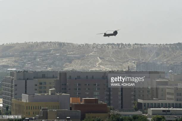 Chinook military helicopter flies above the US embassy in Kabul on August 15, 2021. Several hundred employees of the US embassy in Kabul have been...