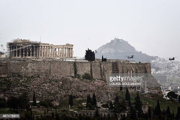 Chinook military transport helicopters fly next to the Acropolis in Athens during a military parade marking Greece's Independence Day on March 25...