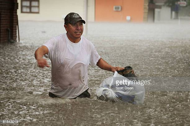 Chinto Roma walks down the street in a driving rain after taking belongings from his flooded home June 12, 2008 in Cedar Rapids, Iowa. The city is...