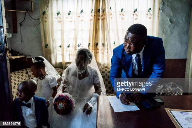 TOPSHOT Chinyere and her husbandtobe Jones prepare wedding documents during a service at the Evangelic Calvary Life Mission Church on May 28 2017 in...