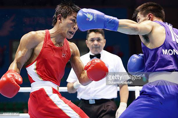 Chinzorig Baatarsukh of Mongolia fights Dennis Galvan of Philippines during the men's light fly boxing preliminaries on day six of the 2014 Asian...