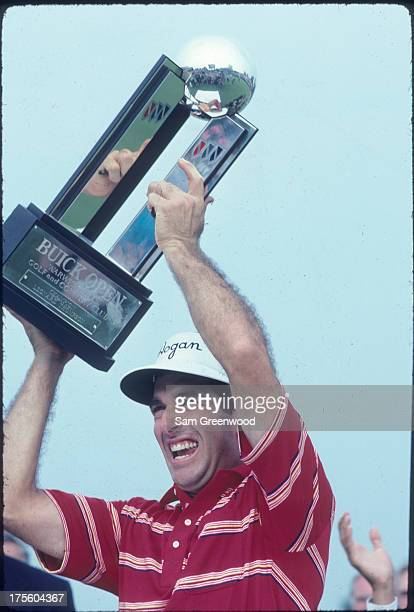 Chip Beck holds up the trophy after winning the final round of the Buick Open at Warwick Hills Golf and Country Club on July 29 1990 in Grand Blanc...