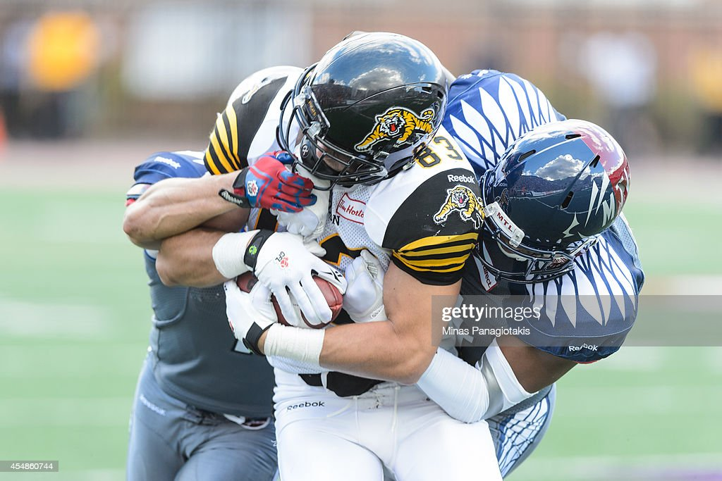 Chip Cox #11 and Kyries Hebert #34 of the Montreal Alouettes tackle Andy Fantuz #83 of the Hamilton Tiger-Cats during the CFL game at Percival Molson Stadium on September 7, 2014 in Montreal, Quebec, Canada.