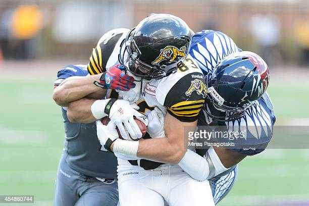 Chip Cox and Kyries Hebert of the Montreal Alouettes tackle Andy Fantuz of the Hamilton TigerCats during the CFL game at Percival Molson Stadium on...
