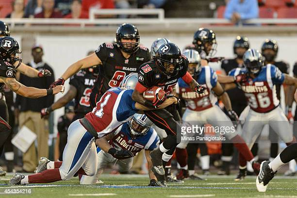 Chip Cox of the Montreal Alouettes holds onto Jamill Smith of the Ottawa Redblacks during the CFL game at Percival Molson Stadium on August 29 2014...