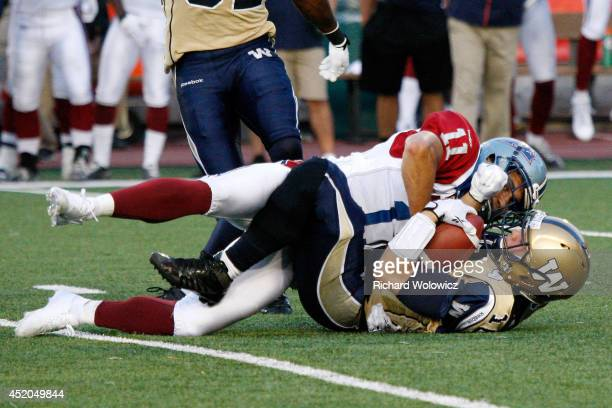 Chip Cox of the Montreal Alouettes tackles Robert Marve of the Winnipeg Blue Bombers during the CFL game at Percival Molson Stadium on July 11 2014...