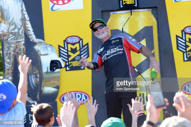 Chip Ellis NHRA Pro Stock Motorcycle throws a hat to the crowd during prerace festivities before the start of the NHRA AAA Midwest Nationals on...