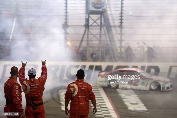 Chip Ganassi Racing crew members celebrate as Kyle Larson driver of the Target Chevrolet performs a burnout after winning the Monster Energy NASCAR...