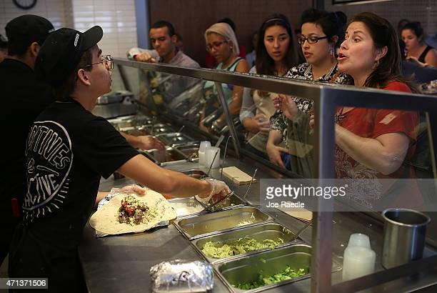 Chipotle restaurant workers fill orders for customers on the day that the company announced it will only use nonGMO ingredients in its food on April...