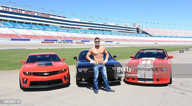 Chippendales dancer Nathan Minor poses in front of Chevrolet Camero ZL1 Dodge Challenger SRT8 392 and a Ford Mustang Shelby GT350 at the American...