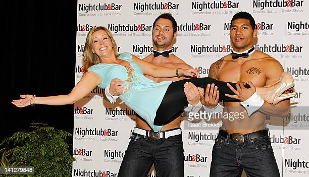 Chippendales dancers James Davis and Nate Estimada hold Nicole Taffer as they arrive at the 27th annual Nightclub Bar Convention and Trade Show at...