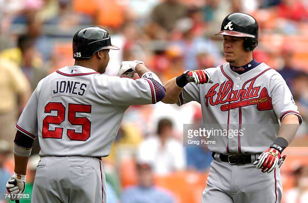 Chipper Jones is congratulated by Andruw Jones of the Atlanta Braves after hitting a home run against the Washington Nationals at RFK Stadium May 17...