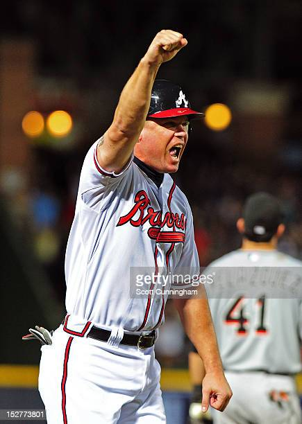 Chipper Jones of the Atlanta Braves celebrates as Freddie Freeman hits a 9th inning walk off home run against the Miami Marlins at Turner Field on...