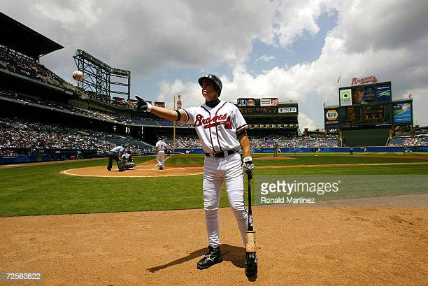 Chipper Jones of the Atlanta Braves throws a ball to a fan during play against the Kansas City Royals on June 17 2004 at Turner Field in Atlanta...