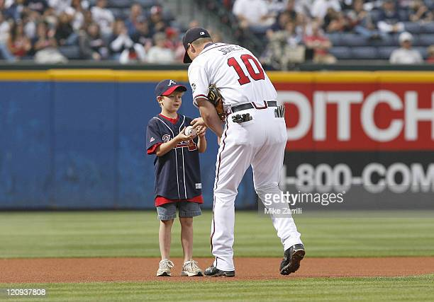 Chipper Jones signs an autograph for a young fan before the game between the Atlanta Braves and the Los Angeles Dodgers at Turner Field in Atlanta GA...