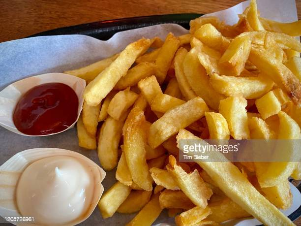 chips, french fries with ketchup and mayonnaise - hot and greasy. - fast food french fries stock pictures, royalty-free photos & images