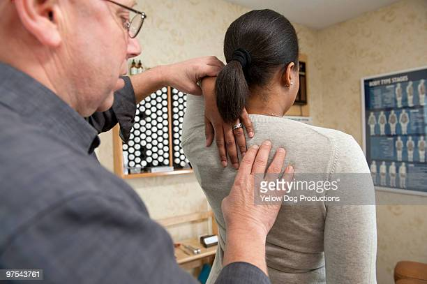 chiropractor examining patient - newhealth stock pictures, royalty-free photos & images