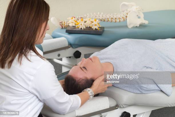 Chiropractor manually adjusts a woman's neck