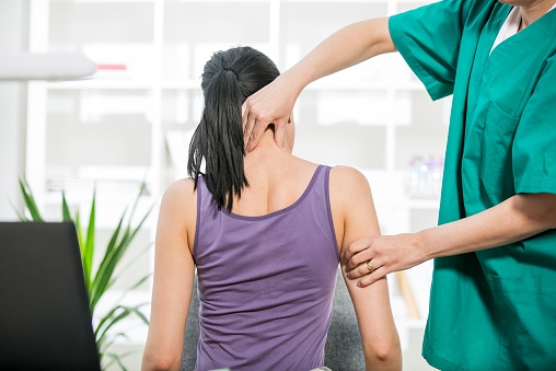 Chiropractor stretches female patient neck muscles 469144560