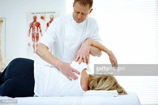 Chiropractor treating shoulder joint problem of a patient