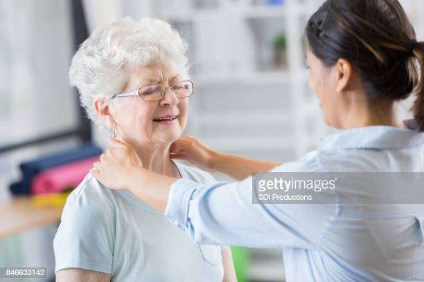 Chiropractor works on senior woman's neck