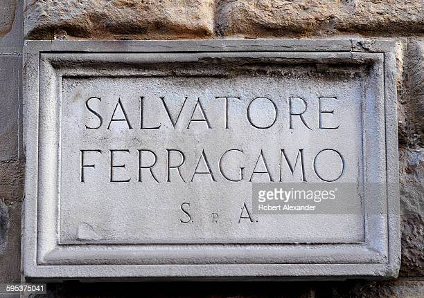 Chiseled stone sign marks the entrance to the Salvatore Ferragamo store and museum on Via Tornabuoni in Florence, Italy. The Italian show designer,...