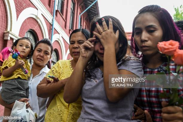 Chit Su Win wife of jailed Myanmar journalist Kyaw Soe Oo grieves with family members while her daughter Mar Mar Latt looks on outside the court on...