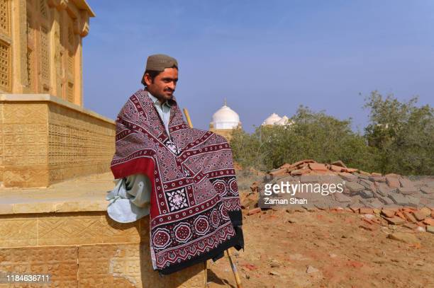chitory graveyard mirpur khas sindh pakistan asia, a sindhi boy with tradination look, ajrak and topi, during daylight sitting on ground of tomb of talpur mirs of chitory graveyard sindh pakistan. - sindhi culture stock photos and pictures