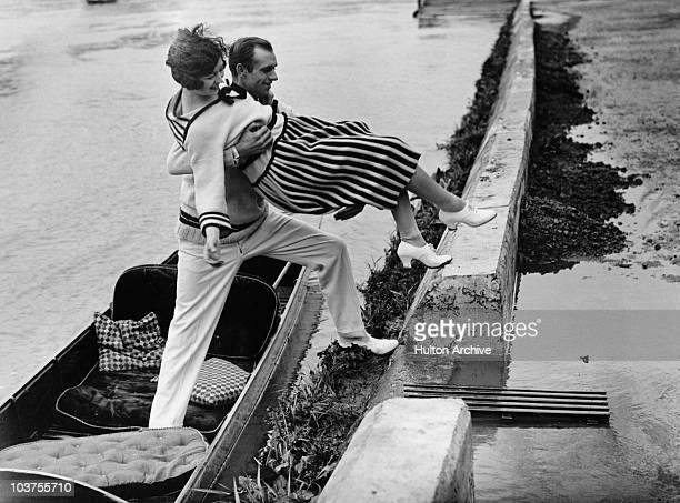 A chivalrous gentleman helps his lady friend onto the towpath from a punt at Richmond London 1925
