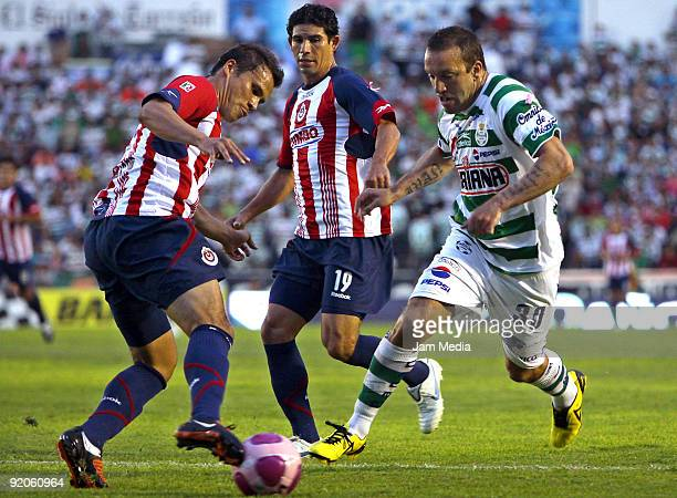 Chivas' Aaron Galindo and Jonny Magallon vies for the ball with Santos' Matias Vuoso during their match in the Apertura 2009 tournament the Mexican...