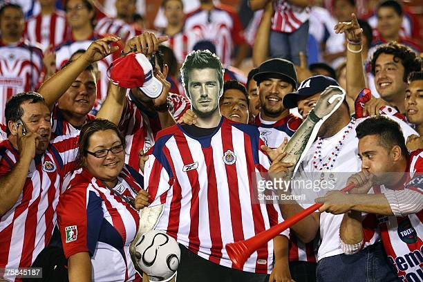 Chivas de Guadalajara fans pose for a photo with a mask of David Beckham after Chivas de Guadalajara defeated the Los Angeles Galaxy 2-1 in their...