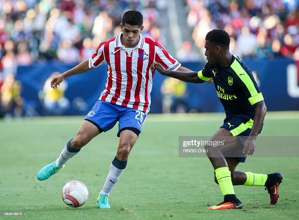 Chivas Guadalajara defender Carlos Villanueva (L) controls the ball against Arsenal during their friendly soccer match at StubHub Center in Carson, California on July 31, 2016. Arsenal won 3-1. / AFP / RINGO