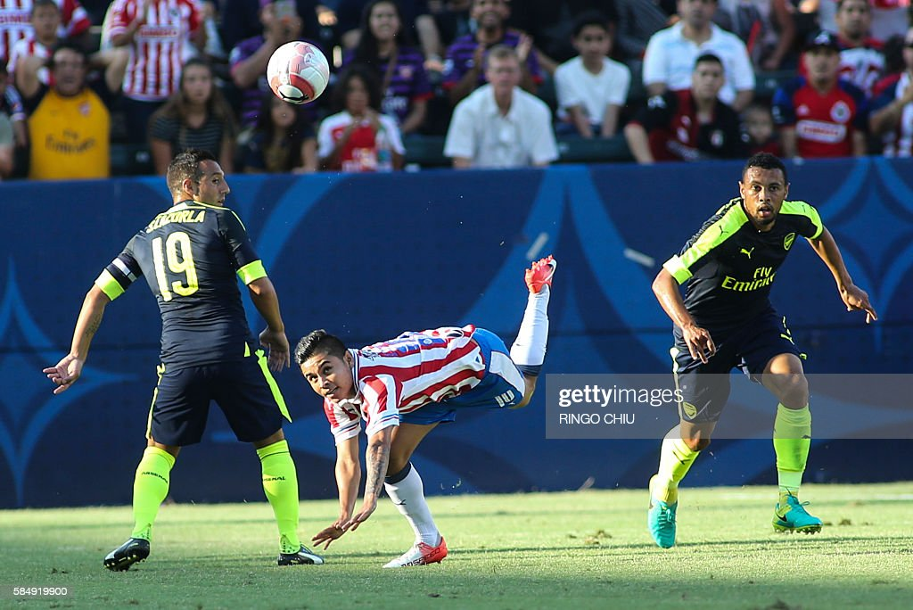 Chivas Guadalajara midfielder Javier Eduardo Lopez (C) defended by Arsenal midfielders Santi Cazorla (L)and Francis Coquelin (R) during their friendly soccer match at StubHub Center in Carson, California on July 31, 2016. Arsenal won 3-1. / AFP / RINGO