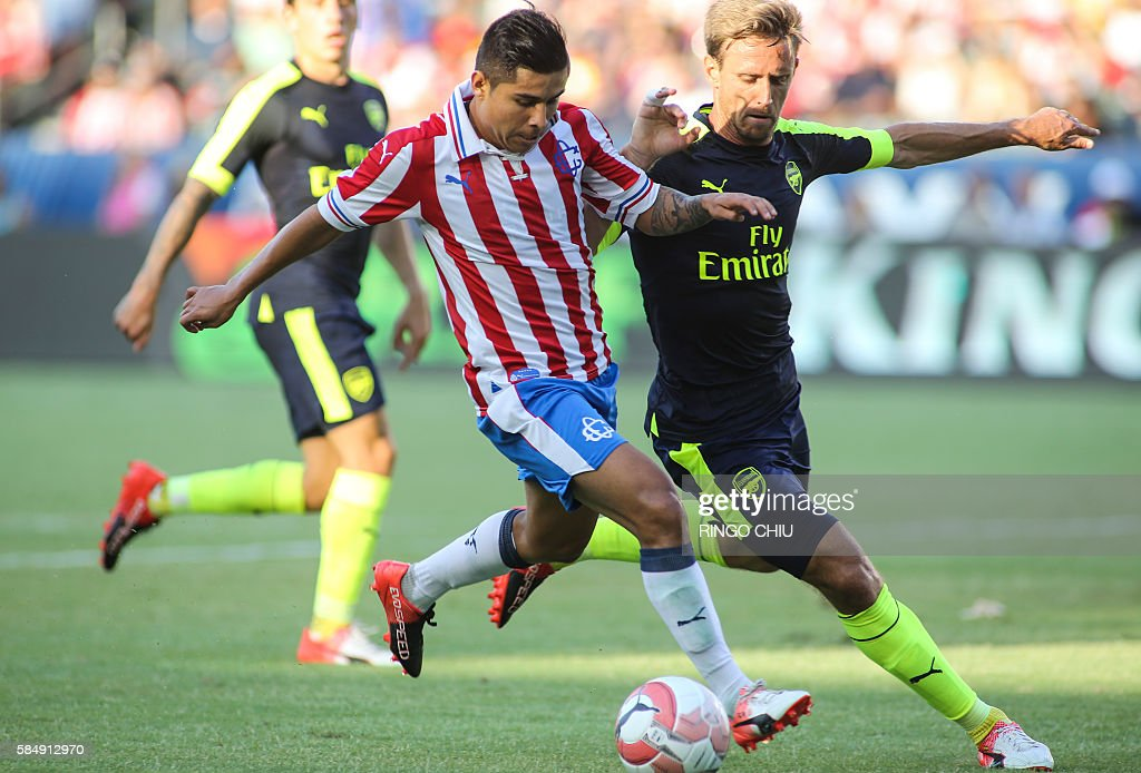 Chivas Guadalajara midfielder Javier Eduardo Lopez (L) drives the ball against Arsenal during their friendly soccer match at StubHub Center in Carson, California on July 31, 2016. Arsenal won 3-1. / AFP / RINGO