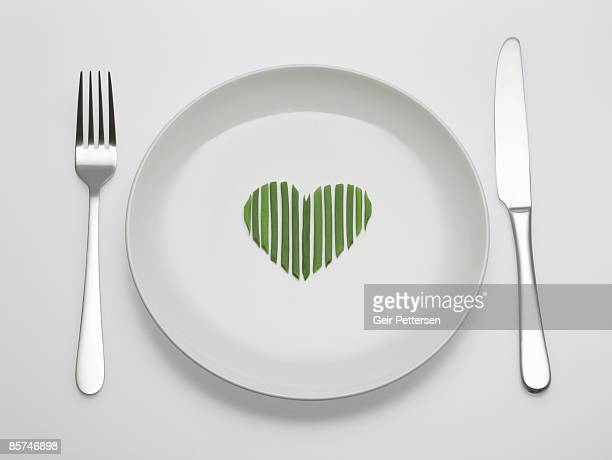 chives arranged in a heart shape on plate - forchetta foto e immagini stock
