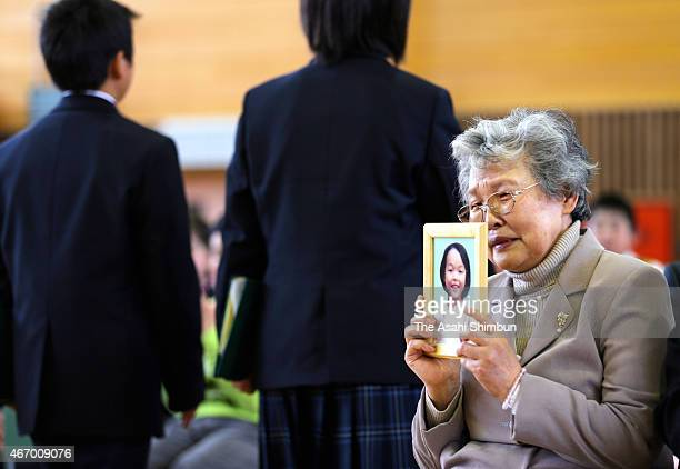 Chiyomi Kikuchi raises the portrait of her granddaughter Keito Kumagaya as guraduates leave after the graduation ceremony of Yonesaki Elementary...