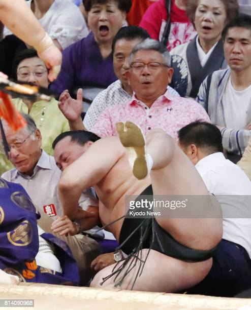 Chiyoshoma falls off the dohyo ring after being beaten by Tochiozan in the Aichi Prefectural Gymnasium on July 13 the fifth day of the 15day Nagoya...