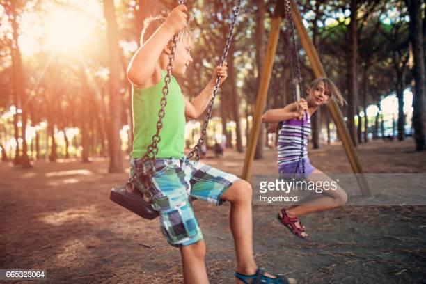 Chlidren swinging in pine forest playground