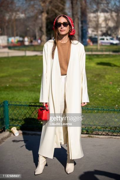 Chloé Harrouche wearing a brown sweater white pants white long jacket white boots red bag and red hair scarf is seen outside Maison Margiela on Day 3...
