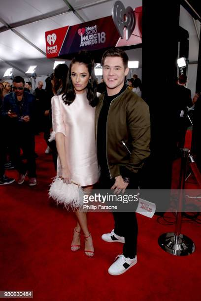 Chloe Bridges and Adam DeVine attend the 2018 iHeartRadio Music Awards which broadcasted live on TBS TNT and truTV at The Forum on March 11 2018 in...