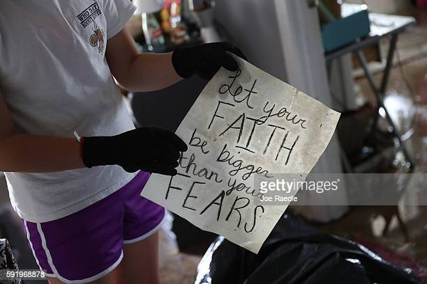 Chloe Cannon holds a sheet of paper that reads, 'Let your faith be bigger than your fears', as she recovers items from her flooded bedroom on August...