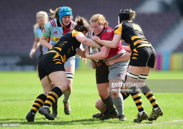 Chloe Edwards of Harlequins Ladies is tackled by Amy Cokayne and Alice Sheffield of Wasps FC Ladies during the Premier 15s Semi Final 2nd Leg between...