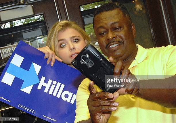 Chloe Grace Moretz makes a funny face while taking a selfie with Hillary Clinton Michigan campaign organizer Gregory Williams during a voter...