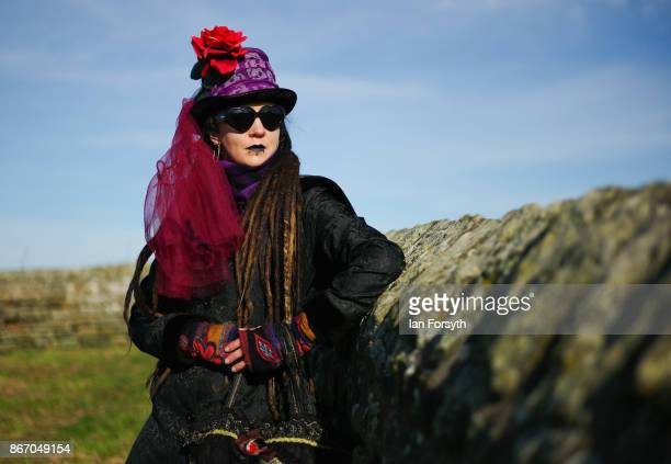 Chloe Hardy from Inverness looks over a wall at Whitby Abbey as she attends the Whitby Goth Weekend on October 27, 2017 in Whitby, England. The...
