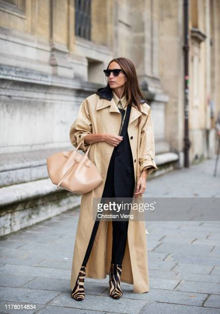 Chloe Harrouche is seen wearing beige trench coat bag black suit beige button shirt beige bag animal print boots during Paris Fashion Week Womenswear...