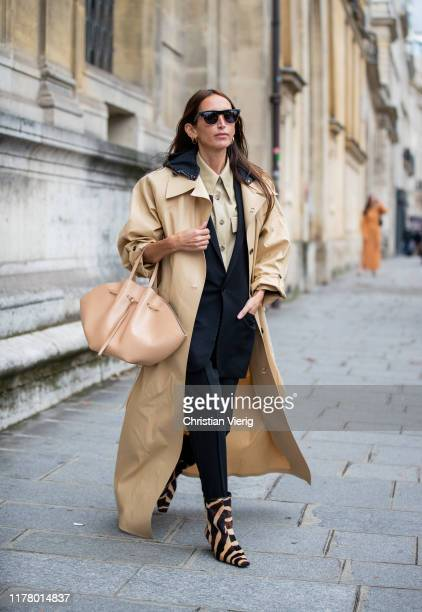Chloe Harrouche is seen wearing beige trench coat, bag, black suit, beige button shirt, beige bag, animal print boots during Paris Fashion Week...
